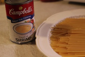 Condensed cream of shrimp soup and spaghetti, broken into thirds.