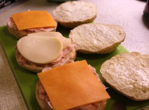 Sliced turkey and sliced cheese placed on the split rolls.