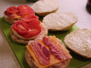 Lay on the bacon and tomato slices.