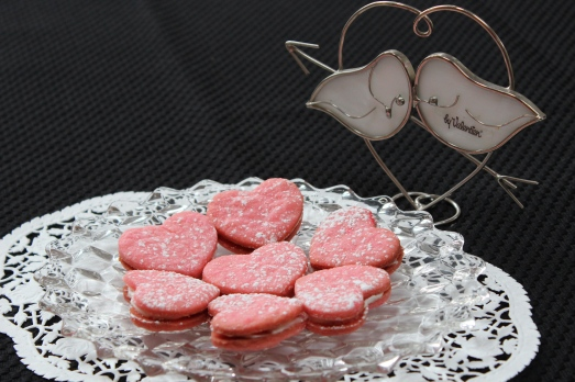 Pink heart sandwich cookies with cream filling.