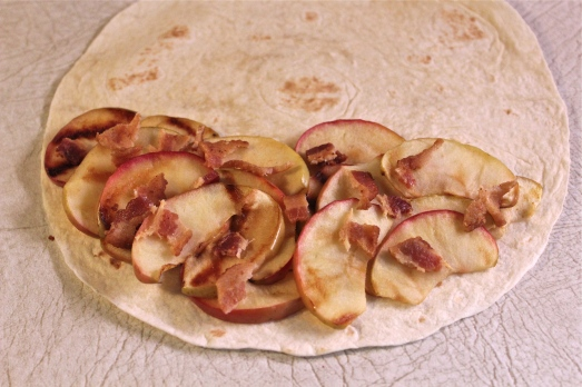Spread a layer of apples and bacon on half the tortilla.