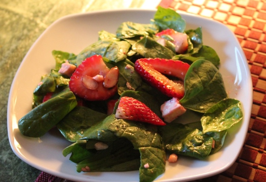 A salad of spinach, strawberries, goat cheese and almonds.