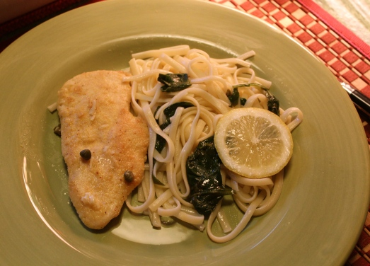 Chicken Piccata served with pasta and spinach.