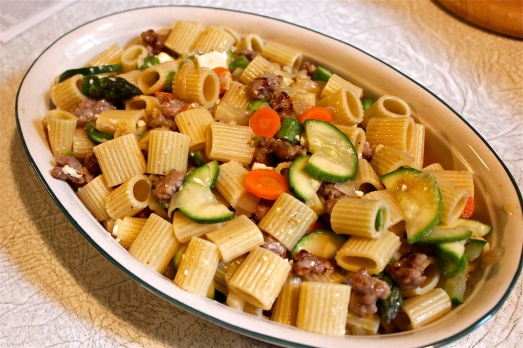 Mix pasta with vegetables and sausage in a baking dish.
