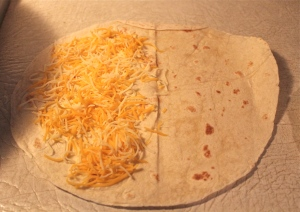 Sprinkle grated cheese on half of each tortilla.