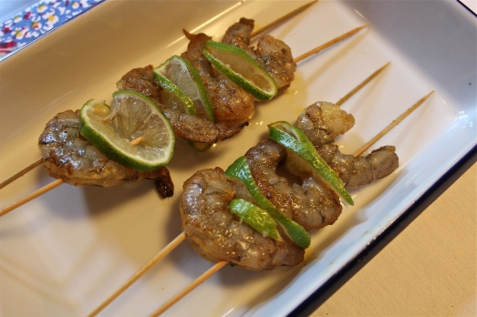 Thread shrimp on double skewers, separating each one with a lime slice.