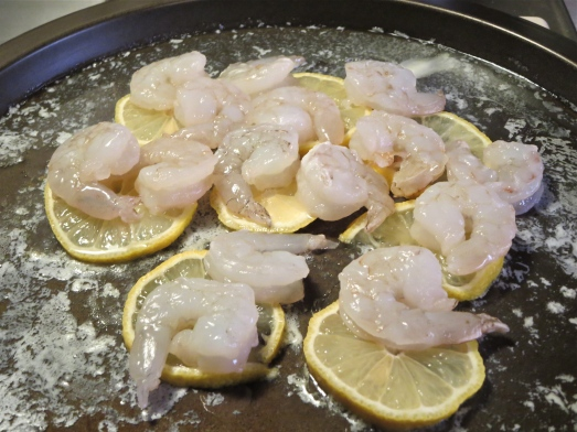 Lay shrimp on top of lemons and melted butter.