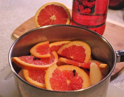 Cut-up pears, orange slices and cloves in the saucepan.