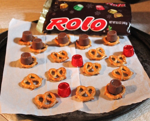 Lay out pretzels on a baking sheet, top each one with a candy.