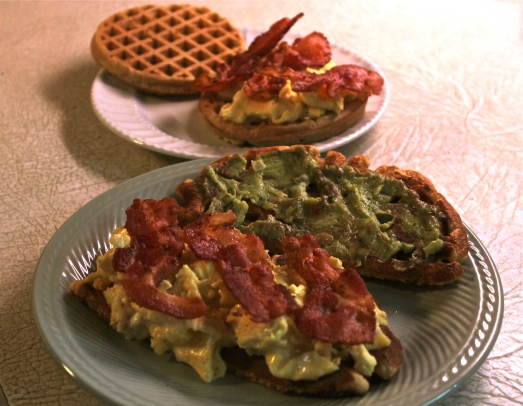 Layering up a sandwich on a whole grain waffle.