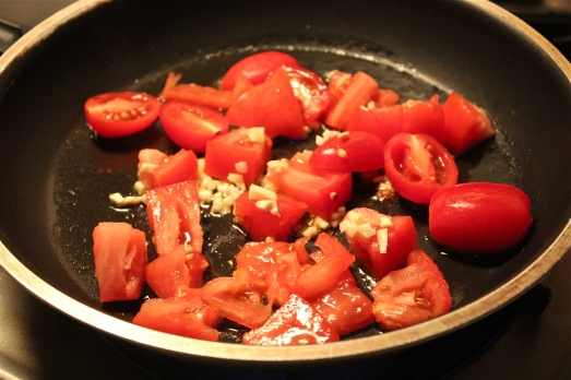 Sautéing the tomatoes and garlic.