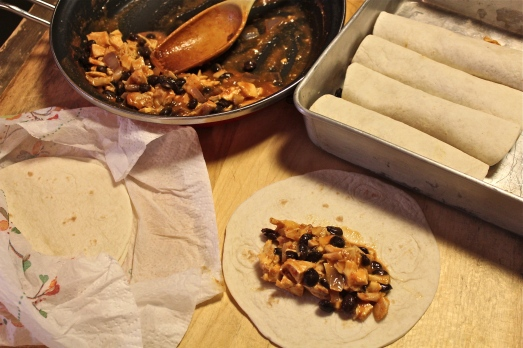 Rolling up the tortillas with filling.