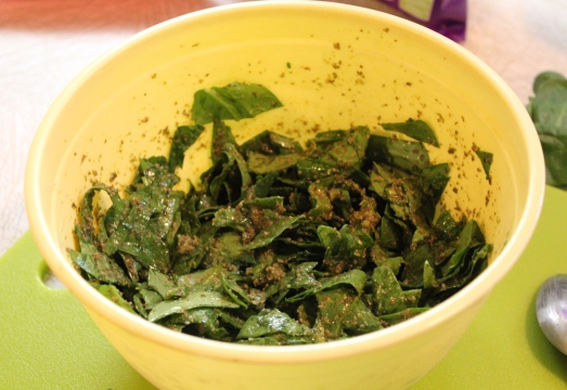 Mixing spinach with pesto.