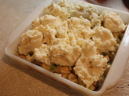 Drop mounds of mashed potato over the filling and spread it out.