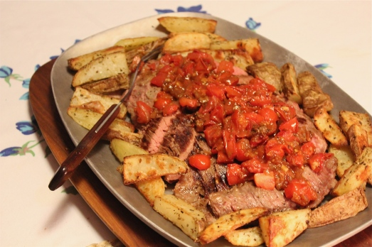 Steak and  tomatoes with roast potatoes.