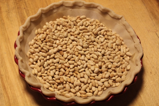 Fill pie shell with pie weights and bake till set.